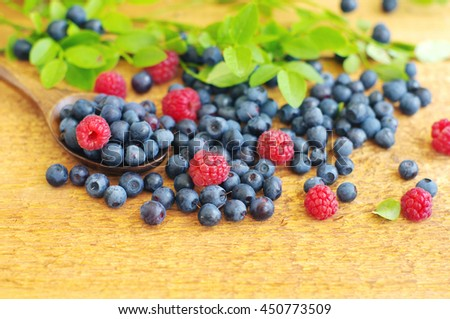 Juicy mature berries of bilberry and raspberry in in a wooden spoon on a wooden surface. - stock photo