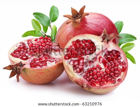 Juicy opened pomegranate with leaves. Isolated on a white background. - stock photo