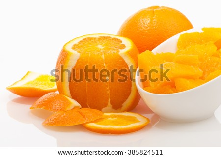 Juicy orange fillets in porcelain bowl decorated with oranges and peel on white background; Ingredient for delicious sweet dessert or marmalade; Vitamin provider - stock photo