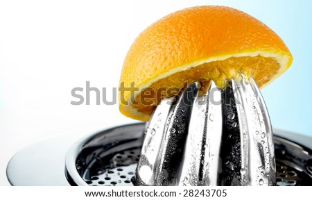 Juicy Orange squeezed out on a juice extractor - stock photo