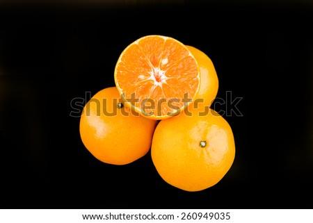 juicy oranges on a black background - stock photo