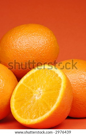Juicy oranges set against orange background