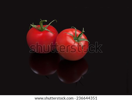 Juicy organic Cherry Tomatoes isolated on black Cherry tomatoes are perfect for salads, soups, sandwiches, or just popped into your mouth for a tasty, healthy snack. - stock photo