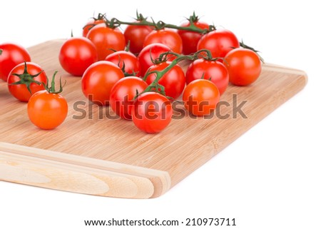 Juicy organic cherry tomatoes on platter. Isolated on a white background. - stock photo