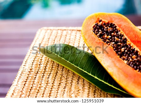juicy papaya and a leaf of a tropical tree on the wicker chair near the swimming pool - stock photo