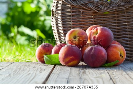 juicy peaches on wooden table in garden - stock photo
