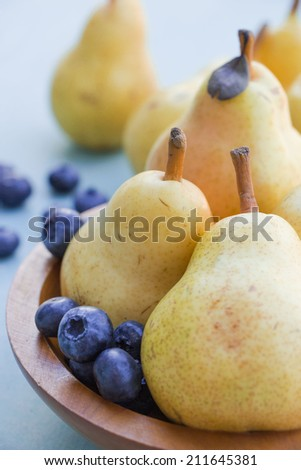Juicy pears in bowl with fresh blueberry, selective focus - stock photo