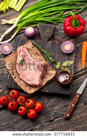 juicy piece of pork on the bone with vegetables on a cutting board on a dark rustic table, top view with copy space. Raw ingredients for cooking delicious and healthy food - stock photo