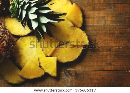 Juicy pineapples slices on wooden table - stock photo
