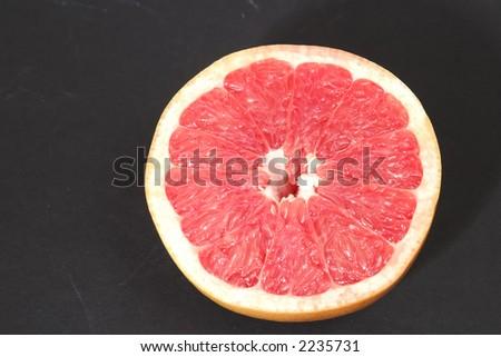 Juicy pink grapefruit half - stock photo