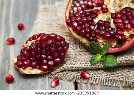 juicy pomegranate on a old wood background - stock photo