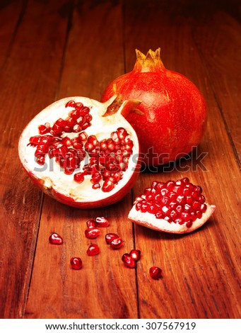 juicy pomegranate open on wood board. Filtered image: warm cross processed vintage effect. - stock photo