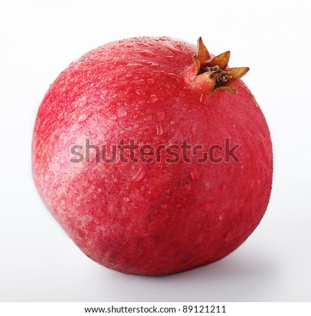 Juicy pomegranate with waterdrops. Isolated on a white background. - stock photo