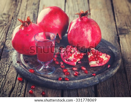Juicy pomegranates,whole and broken and pomegranate juice on wooden background. Toned image. Vintage style.Copy space.selective focus.  - stock photo