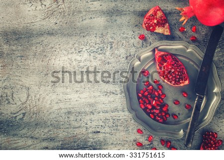 Juicy pomegranates,whole and broken vintage on a metal plate.Toned image. Vintage style.Copy space.selective focus. - stock photo