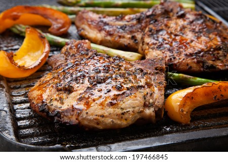 Juicy pork chops are grilled on griddle with asparagus and bell pepper. Backyard grilling for summer picnic.