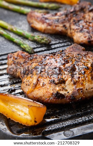 Juicy pork chops are grilled on griddle with asparagus and bell pepper. Backyard grilling for summer picnic.  - stock photo