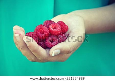 juicy raspberries in young girl's hand - stock photo
