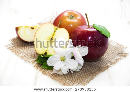Juicy red apple with blossom on sack background - stock photo