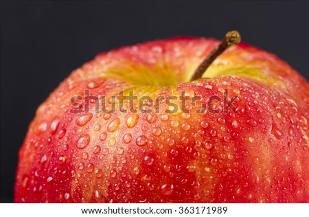 juicy red apple with water droplets on a black background - stock photo