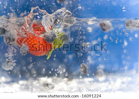 Juicy red strawberries and blueberries plunging into some water. - stock photo