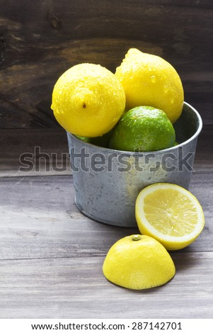 Juicy ripe citrus lime and lemon in steel bucket - stock photo
