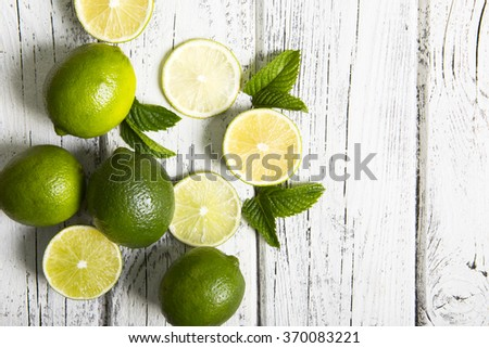 Juicy ripe citrus on an old wooden table - lime and mint - stock photo