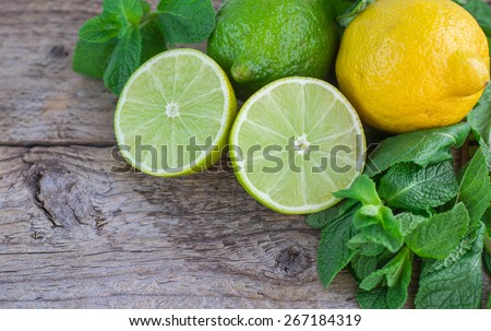 Juicy ripe citrus on an old wooden table - lime, lemon and mint - stock photo