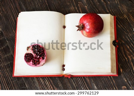 juicy ripe pomegranate on opened book. Rustic style - stock photo
