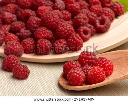 Juicy ripe raspberry on a wooden plate with a spoon and a green leaf - stock photo
