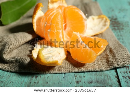 Juicy ripe tangerine with leaves on wooden table  - stock photo