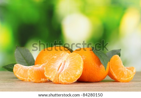 Juicy ripe tangerines with cloves on wooden table outdoors - stock photo