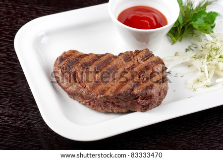 Juicy roasted beef steak with vegetables closeup at plate