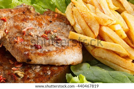 Juicy roasted pork steak with french fries, vegetables and spices - stock photo