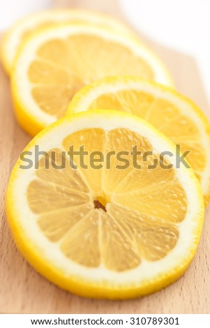 Juicy slices of lemon on a cutting board, closeup - stock photo