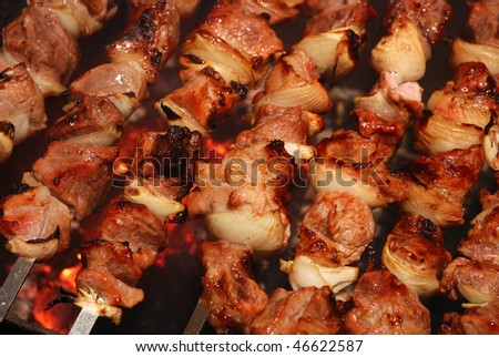 Juicy slices of meat with sauce prepare on fire - stock photo