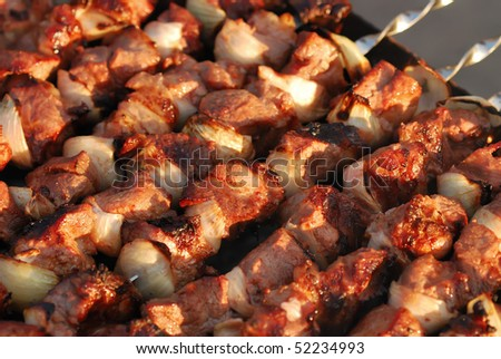 Juicy slices of meat with sauce prepare on fire
