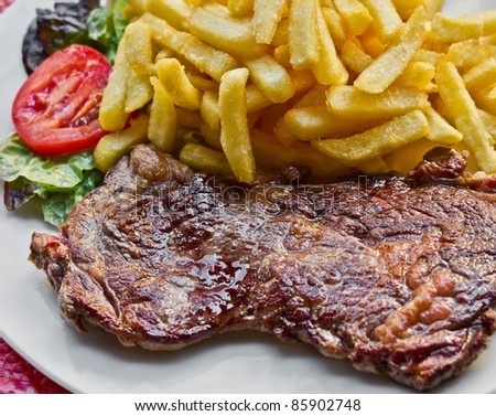 juicy steak beef meat with tomato and french fries - stock photo