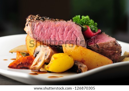 Juicy steak with baked potatoes and mushrooms, Dry aged prime grade beef rib eye steak cooked medium rare. Steak cut fries, pepper, mushrooms and parsley on a plate - stock photo