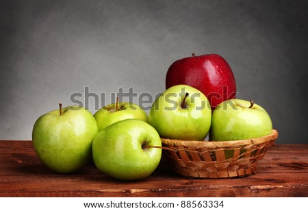 juicy sweet apples in basket on wooden table on gray background - stock photo
