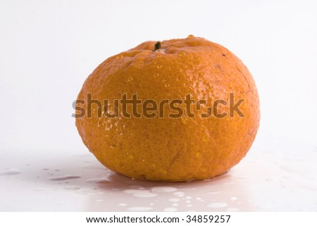 Juicy tangerine covered by drops of water. Isolated on white background