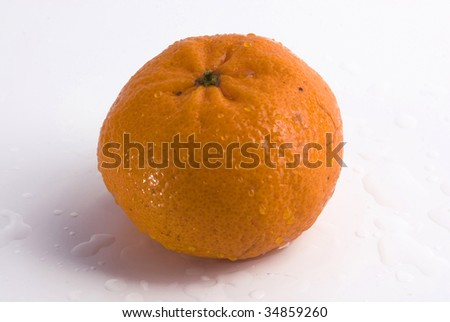 Juicy tangerine covered by drops of water. Top view. Isolated on white background