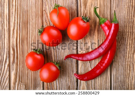 Juicy tomato cherry and red hot chili pepper on the wooden table top view - stock photo
