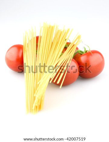 Juicy tomatoes with uncooked spaghetti on a white background. - stock photo