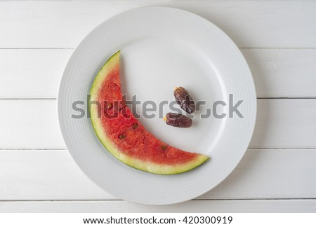Juicy watermelon slice cut into moon shape, arranged on a white plate with two dates. Healthy fasting food during Holy month of Ramadan. - stock photo