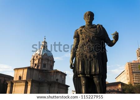 Julius Caesar statue on Fori Imperiali with church of Santi Luca e Martina in background - stock photo