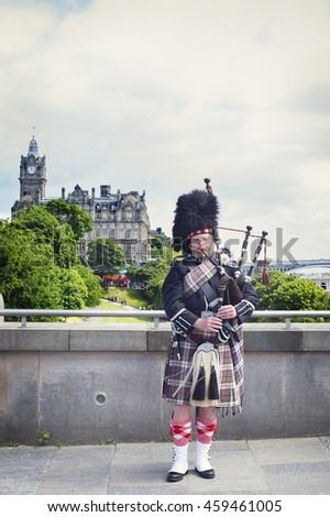 JULY 9, 2016 - EDINBURGH, SCOTLAND Piper playing the bagpipes on the pedestrian bridge to Edinburgh Castle. The historic Balmoral Hotel is in the background. - stock photo