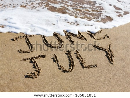 July is coming concept - inscription June and July written on a sandy beach, the wave is starting to cover the word June.  - stock photo