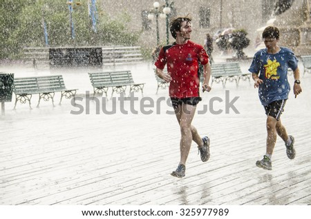JULY 27, 2014 - QUEBEC CITY, CANADA - Two guys run in the heavy rain on a  street of Quebec City, Canada close to Chateau Frontenac. - stock photo
