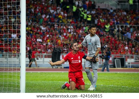 July 24, 2015- Shah Alam, Malaysia: Liverpool's Jordan Henderson (red) appeals to the referee in a friendly match against the Malaysian team. Liverpool Football Club from England is on an Asia tour. - stock photo